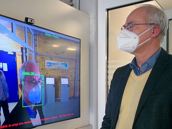 Professor mit FFP2-Maske vor Bildschirm; visuelle Masken-Erkennung funktioniert