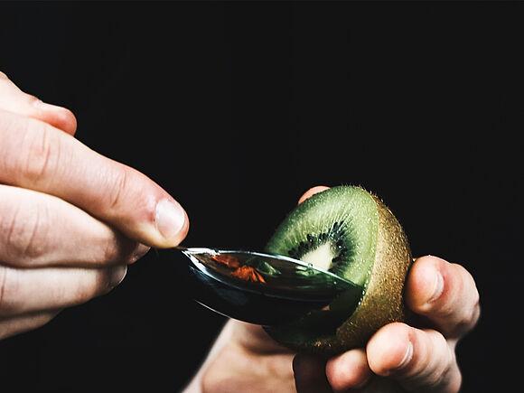 Eine Kiwi wird ausgelöffelt