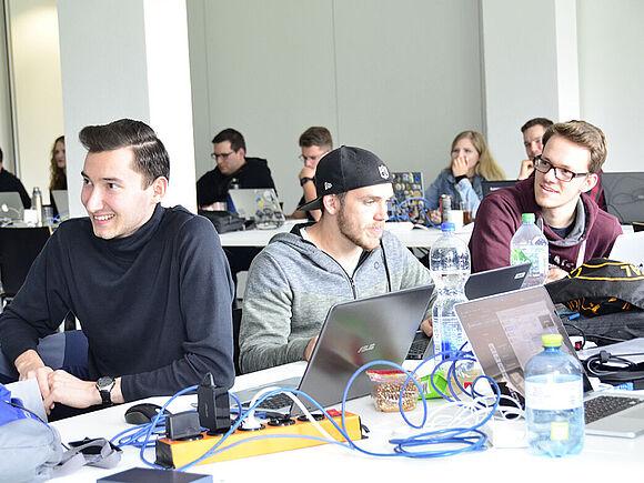 """Studierende arbeiten im Workshop """"Hack2Improve"""" gemeinsam an Laptops"""