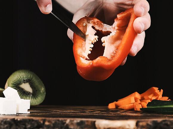 Eine rote Paprika wird geschnitten